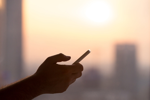 Close-up of hands of young man holding mobile phone, using smartphone app, scrolling. silhouette against sunny street view